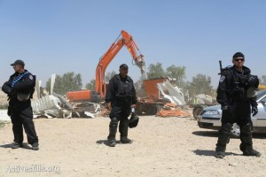 Israeli policemen stand by as a bulldozer demolishes the Bedouin village of Al-Arakib for the 64th time (photo: Activestills.org)